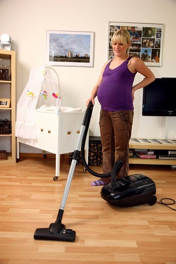 Pregnant woman, 9th month, at home, doing light housework, vacuuming : Stock Photo
