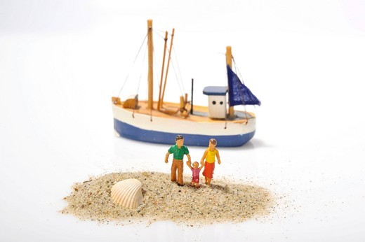 Family figurines in sand in front of a boat : Stock Photo