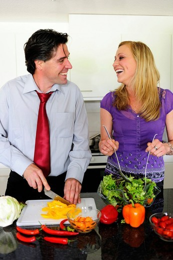 Young couple cutting vegetables for a salad : Stock Photo