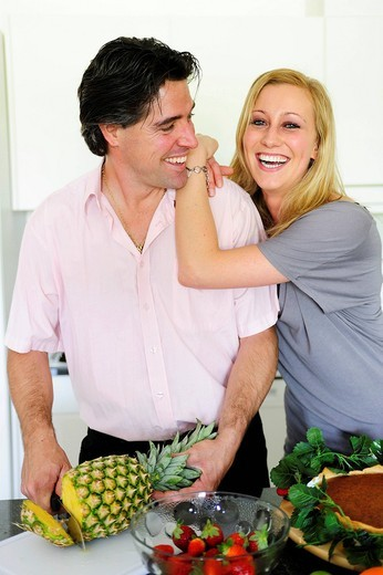 Stock Photo: 1848-481434 Man cutting a pineapple, young woman leaning on his shoulder