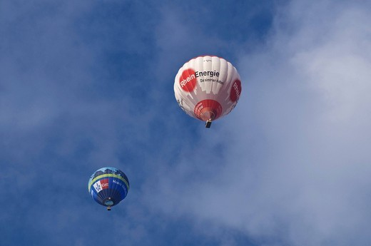 Stock Photo: 1848-484169 Two hot_air balloons, Klett Verlag and Rheinenergie, in front of a cloudy sky