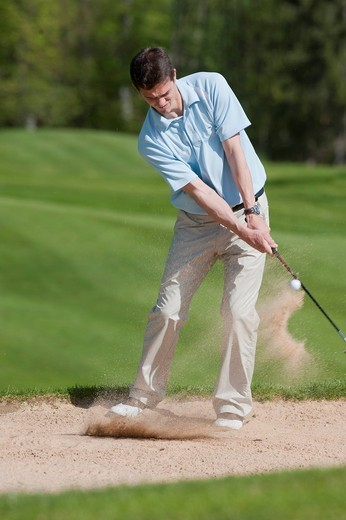 Golfer chipping out of the sand in a bunker, alpine golf course, Achenkirch, Tyrol, Austria, Europe : Stock Photo