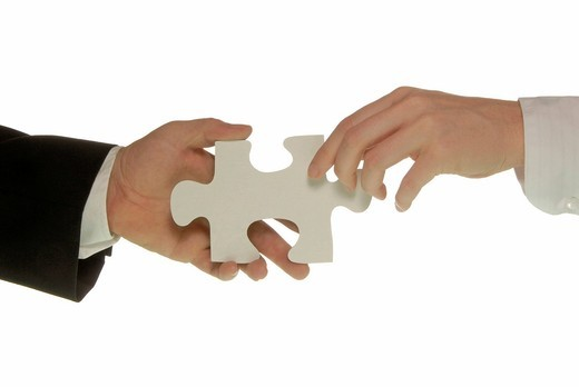 Business man holding a piece of a jigsaw puzzle, business woman reaching for it, symbolic image for cooperation : Stock Photo