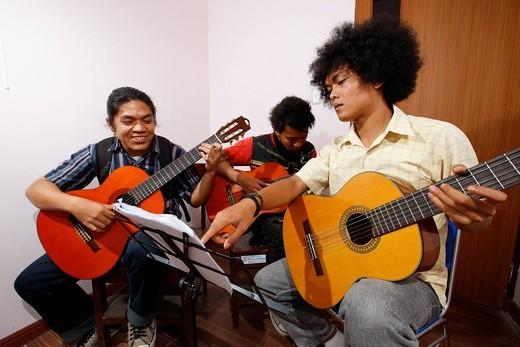Stock Photo: 1848-486556 Students learning to play guitar, HKBP Nommensen University, Medan, Sumatra island, Indonesia, Asia