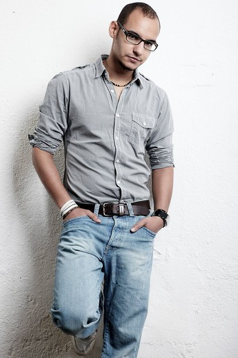 Stock Photo: 1848-486584 Young man with glasses, jeans and shirt is leaning against a wall, hands in his pockets