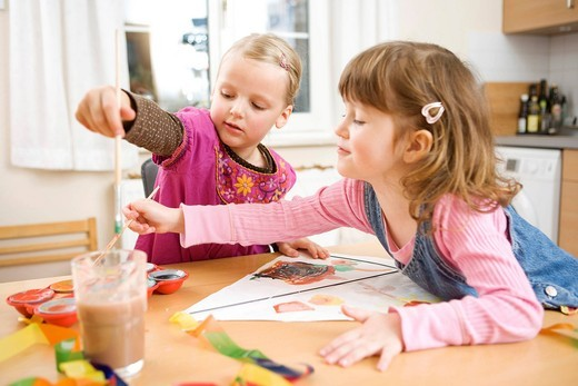 Two girls painting with water colours : Stock Photo