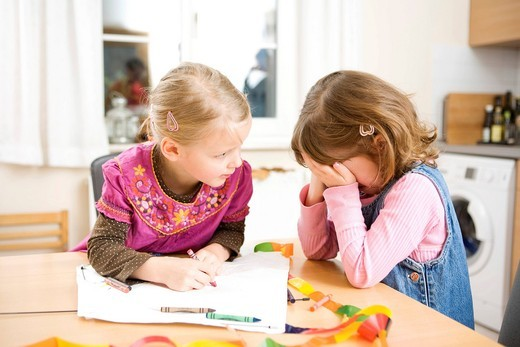 Two girls drawing with wax crayons, one girl crying : Stock Photo