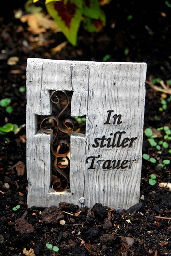 Wooden boad with text In stiller Trauer or in silent mourning, cross, grave, cemetery : Stock Photo