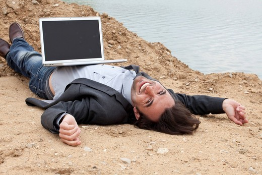 Young man with laptop lying on a lake´s beach laughing : Stock Photo