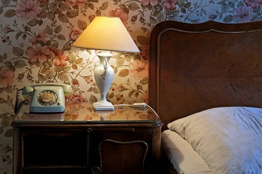 Bedside table with lamp and phone by the bed, former home of silent film star Asta Nielsen, today Pension Funk, Fasanenstrasse, Charlottenburg district, Berlin, Germany, Europe : Stock Photo