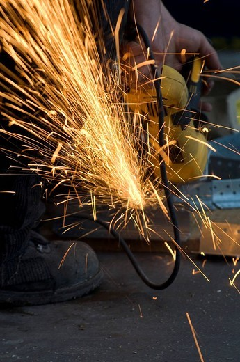Cutting and grinding work with flying sparks : Stock Photo