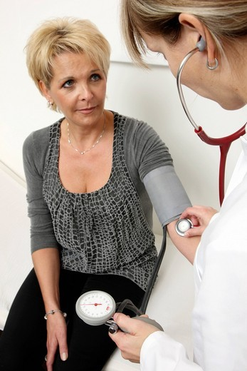 Medical practice, medical technician taking the blood pressure of a patient : Stock Photo