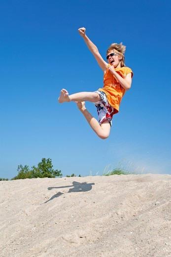Stock Photo: 1848-491009 A young boy laughing and jumping off a dune, Timmendorf, Poel island, Mecklenburg_Western Pomerania, Northern Germany