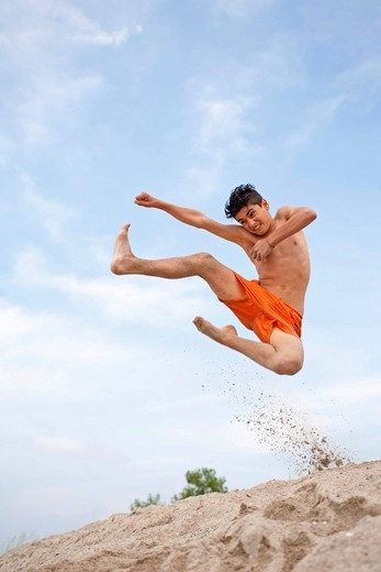 A young boy laughing and jumping off a dune, Timmendorf, Poel island, Mecklenburg_Western Pomerania, Northern Germany : Stock Photo