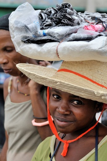 Young female vendor carrying goods on her head, urban market of Des Croix Bossales in the port district of La Saline, Port_au_Prince, Haiti, Caribbean, Central America : Stock Photo