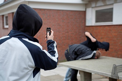 Boy being beaten on the playground while a third films with his cell phone, posed scene : Stock Photo