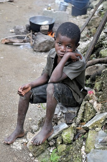 Portrait of a boy with a worried face in front of a fireplace, Palmiste_a_Vin near Leogane, Haiti, Caribbean, Central America : Stock Photo