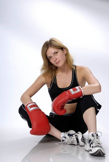 Young woman with boxing gloves sitting on a floor : Stock Photo