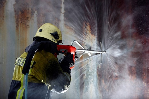 High_pressure extinguishing system, Cobra, the Fire Service Training Centre, Heat, a firefighter demonstrating the possibility of using a high pressure of 300 bar to cut through materials such as concrete or steel to then extinguish a blaze in an inaccess : Stock Photo