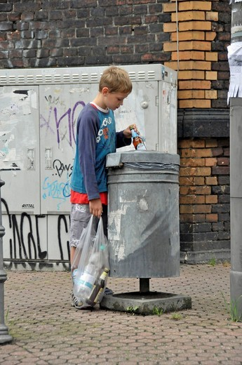 Nine year old boy earning his pocket money by collecting returnable bottles, Germany, Europe : Stock Photo