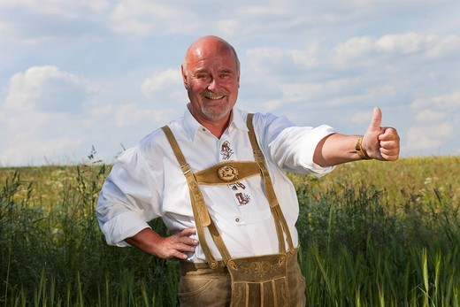 Elderly man wearing traditional Bavarian lederhosen, standing in a cornfield, thumb up, smiling : Stock Photo