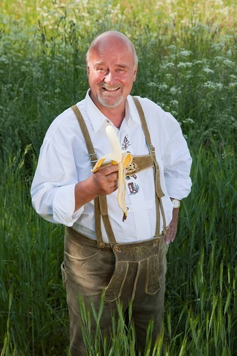 Stock Photo: 1848-495955 Elderly man wearing traditional Bavarian lederhosen, standing in a cornfield, holding a banana