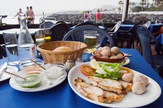 Spanish food in the restaurant, grilled fish with Canarian potatoes, Papas Arrugadas, Souce Mojo Rojo, Mojo Verde, Puerto del Carmen, Lanzarote, Canary Islands, Spain, Europe : Stock Photo