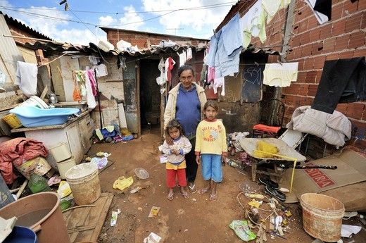 Pregnant woman, 43, lives with her two daughters in front of a shabby shack in a Favela or shanty town, the family lives by collecting, separating and selling recyclable waste, satellite city of Ceilandia near Brasilia, Distrito Federal, Brazil, South Ame : Stock Photo