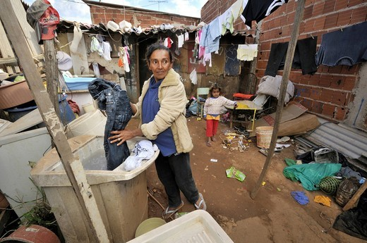 Pregnant woman, 43, washing clothes in front of a shabby shack in a Favela or shanty town, the family lives by collecting, separating and selling recyclable waste, satellite city of Ceilandia near Brasilia, Distrito Federal, Brazil, South America : Stock Photo