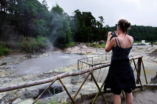 Stock Photo: 1848-497393 Woman taking pictures of fumaroles at Lagoa das Furnas on the island of Sao Miguel, Azores, Portugal
