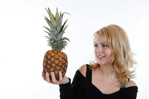 Woman with a pineapple in her hand : Stock Photo