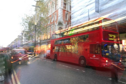 Red London Bus running on Tottenham Court ROad, Oxford Circus, London, UK : Stock Photo