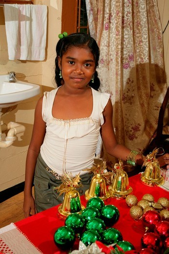 Girl standing in front of a table with Christmas ornaments helping to decorate, Georgetown, Guyana, South America : Stock Photo