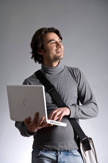 Young man with a bag, holding a laptop : Stock Photo