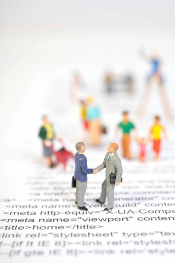 Stock Photo: 1848-529947 Figurines standing on the source code of a website