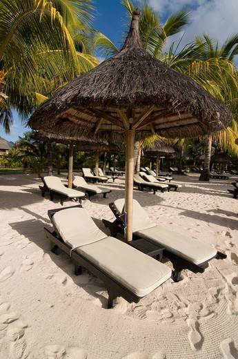 Sunbeds under sunshade on the beach of Le Paradis Hotel, Mauritius, Africa : Stock Photo