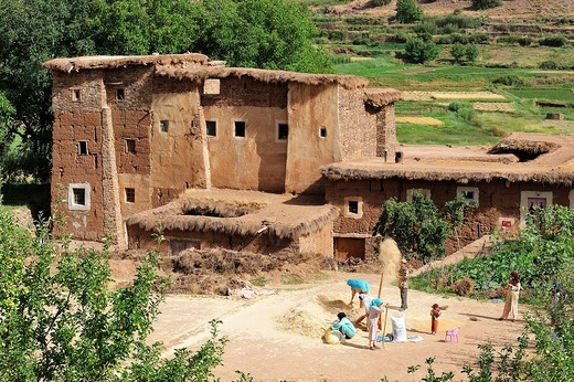 Kasbah, Berber mud fortress, in a square outside the Kasbah, the inhabitants are separating the chaff from the grain, Ait Bouguemez, High Atlas, Morocco, Africa : Stock Photo