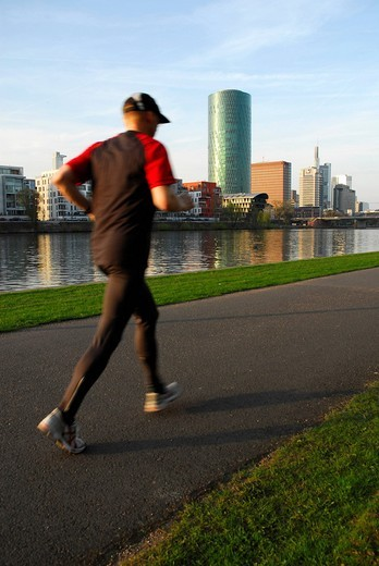 Jogger jogging along the river, Theodor Stern Kai, Westhafen Tower in the Gutleutviertel quarter, skyline of the office district, Frankfurt am Main, Hesse, Germany, Europa : Stock Photo