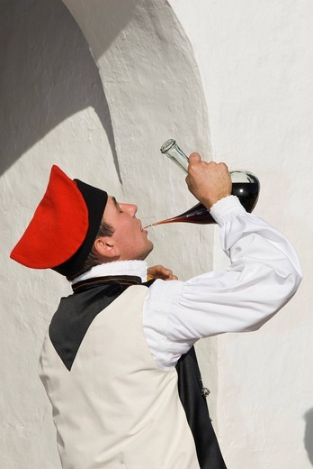Young man in traditional costume drinking wine out of a typical Spanish porron, Ibiza, Spain, Europe : Stock Photo