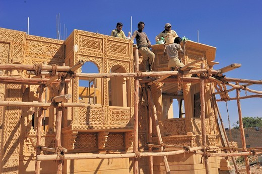 Stock Photo: 1848-534193 Craftsmen working on a simple wooden frame with knotted ropes on an ornate sandstone facade, Jaisalmer, Rajasthan, India, Asia