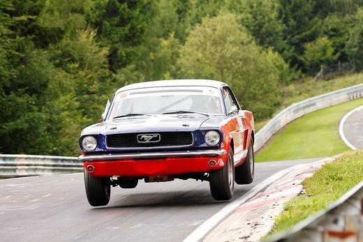 Stock Photo: 1848-536733 Ford Mustang jumping at a jump hill, AC Cobra, Oldtimer Grand Prix Nurburgring 2010 race, Nurburgring race track, Rhineland_Palatinate, Germany, Europe