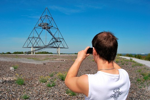 Young man taking pictures of the Tetraeder landmark, a tetrahedron made from steel, with a digital camera, industrial heritage, coal mining tip in Bottrop, Ruhr area, Metropole Ruhr, North Rhine_Westphalia, Germany, Europe : Stock Photo
