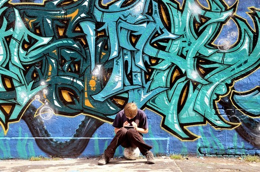 Ten_year_old boy playing with his Nintendo in front of a graffiti wall, Germany, Europe : Stock Photo