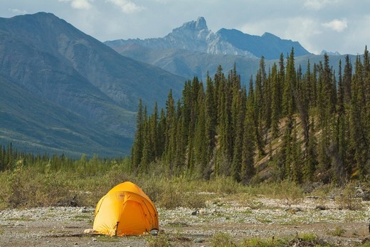 Expedition tent on a gravel bar, Northern Mackenzie Mountains behind, camping, Wind River, Yukon Territory, Canada : Stock Photo