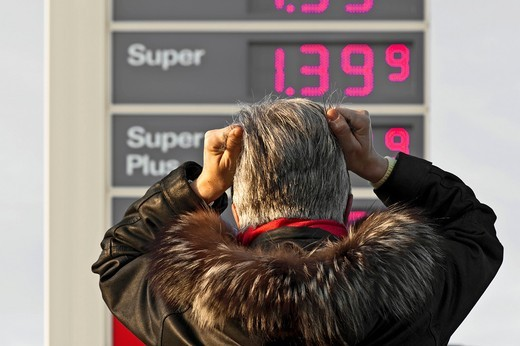Stock Photo: 1848-539143 Woman standing in front of the price board of a gas station and pulling at her hair