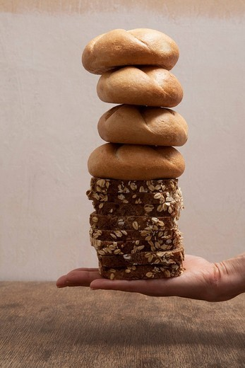 Hand holding a stack of bread rolls and sliced bread : Stock Photo