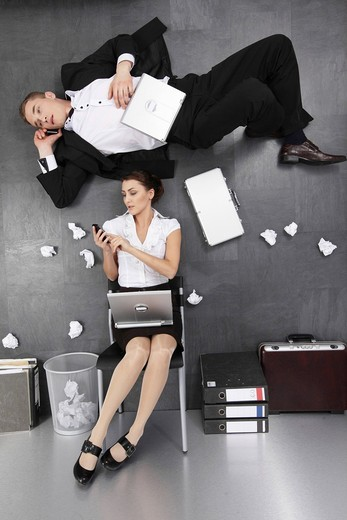 Sitting businesswoman and businessman on the floor, irritating pers : Stock Photo