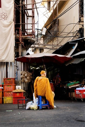 Stock Photo: 1848-541410 Old monk sitting in a street market waiting for people to offer him alms in the morning ritual of Buddhist monks in Chiang Mai, Thailand, Asia