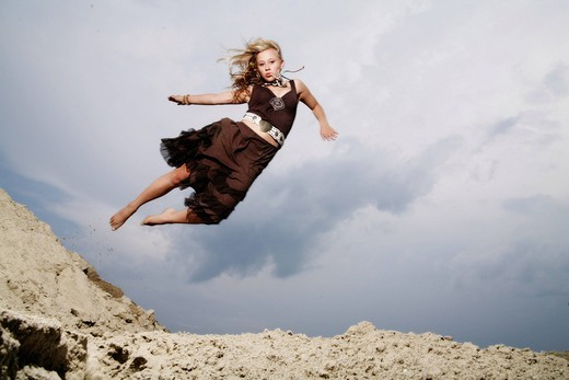 Stock Photo: 1848-541537 Woman jumping from a sand hill