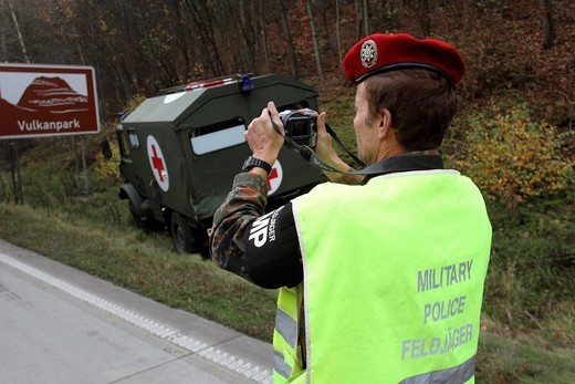 Feldjaeger, a military policeman of the Bundeswehr, Germany´s armed forces, documenting the scene of an accident with a military vehicle on the A61 motorway near Niederzissen, Rhineland_Palatinate, Germany, Europe : Stock Photo